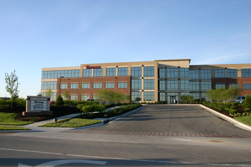 Opus 2 Building in Lenexa.  This building has buff and red panels, each color has areas of sandblast and exposed aggregate finish.  It also uses inlaid tile accents,